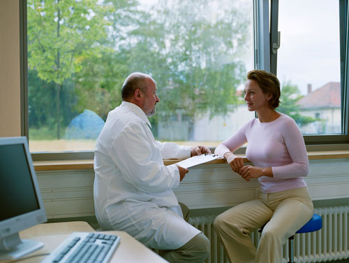 A woman speaking with her oral surgeon about receiving a sinus lift.