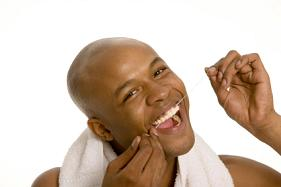 A man happy and flossing his teeth to remove plaque buildup.
